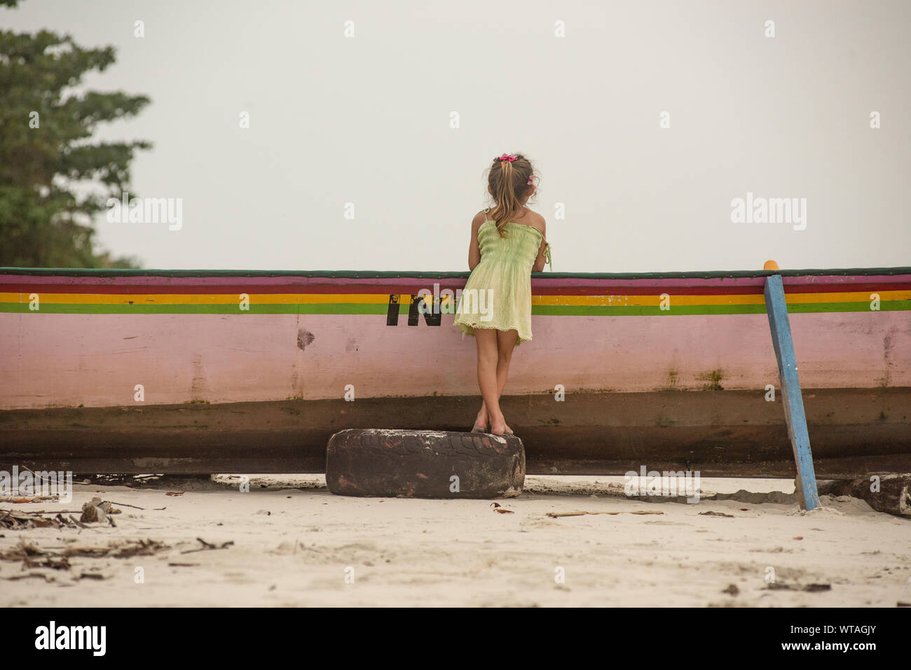 Girl in dress leaning over the fishing boat on the beach Stock Photo
