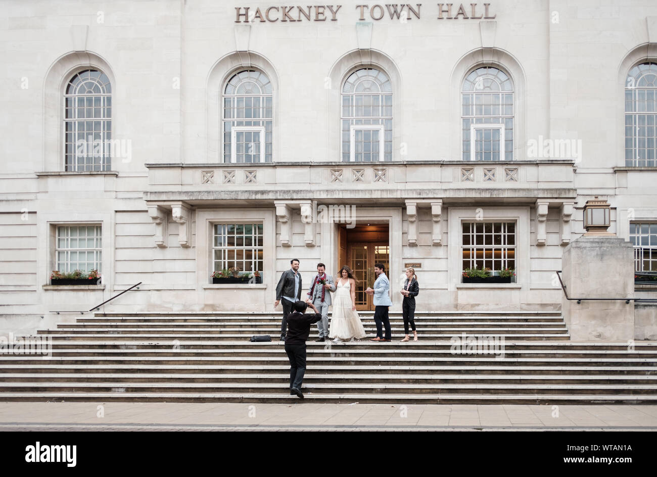 A young, contemporary wedding party leave Hackney Town Hall, East London, UK. Stock Photo