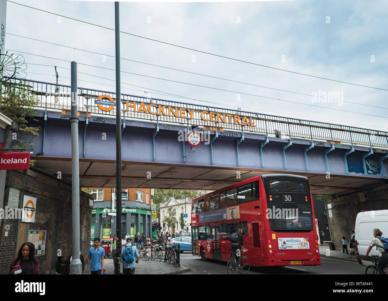 Red London bus passes under a railway bridge with signage for Hackney Central Overground Station at Mare St, Hackney, East London, UK Stock Photo