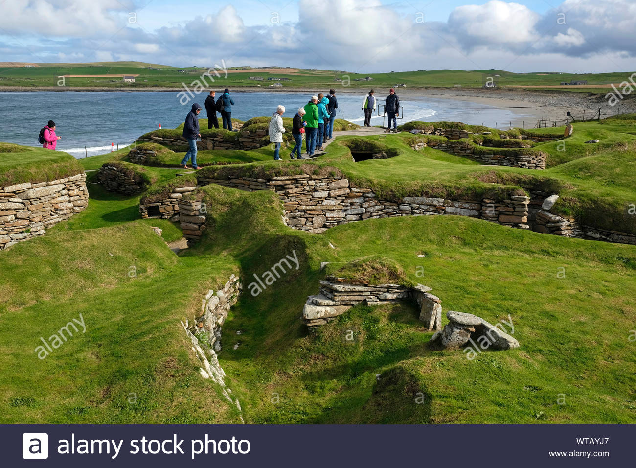 Tourists visiting Skara Brae, a stone-built Neolithic settlement, located on Mainland Orkney, Scotland Stock Photo