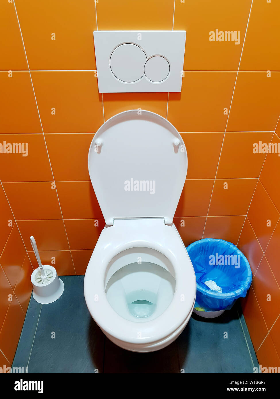 White toilet bowl in the bathroom with orange wall. Cramped little bathroom. Stock Photo