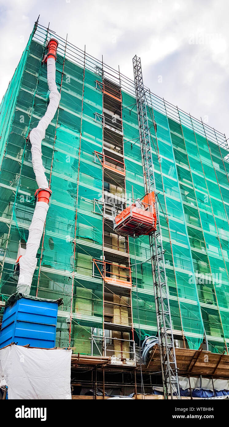 Renovations apartment building with scaffolding, Apartment building thermal insulation mineral wool slabs. Insulated apartment building Stock Photo