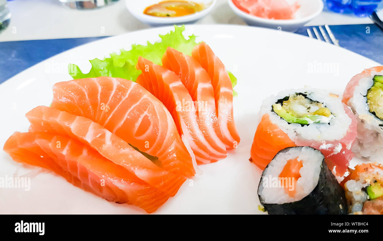Japanese cuisine, Fresh Salmon sashimi and sushi roll with green salad on white plate isolated on white background. Stock Photo