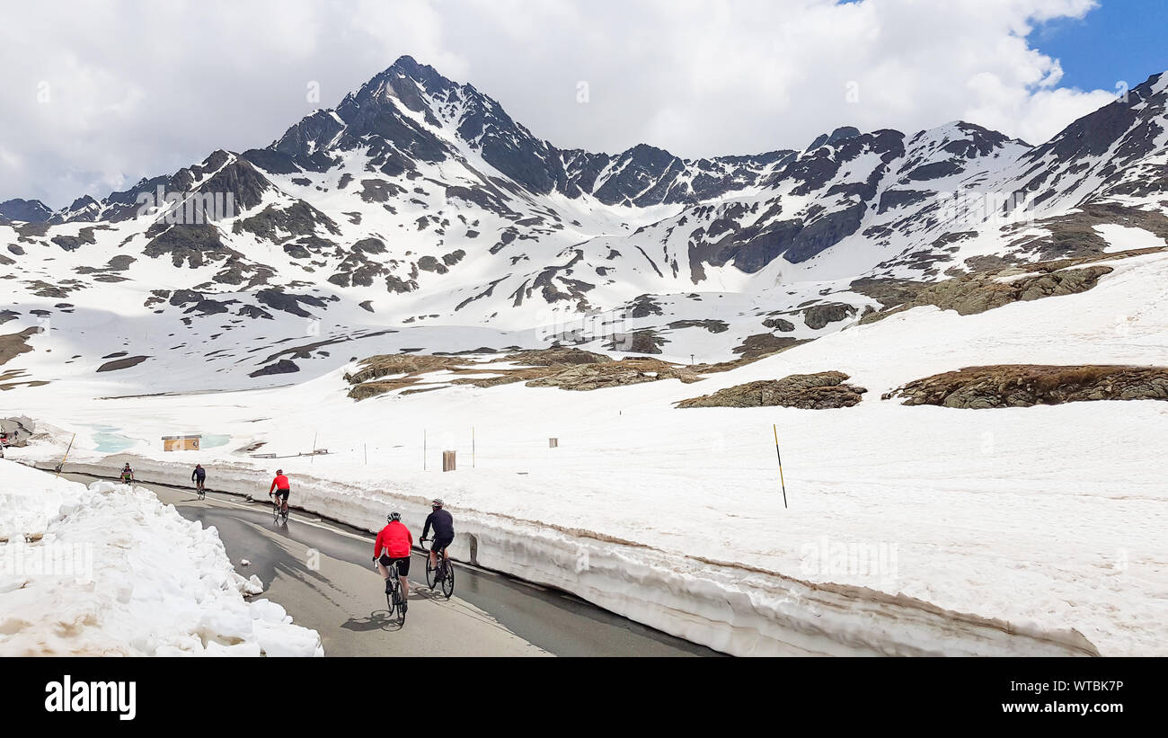 An aerial view of an attractive group of people riding bikes on a road in the mountain view with snow in Dolomite Mountains Landscape, Sport and activ Stock Photo