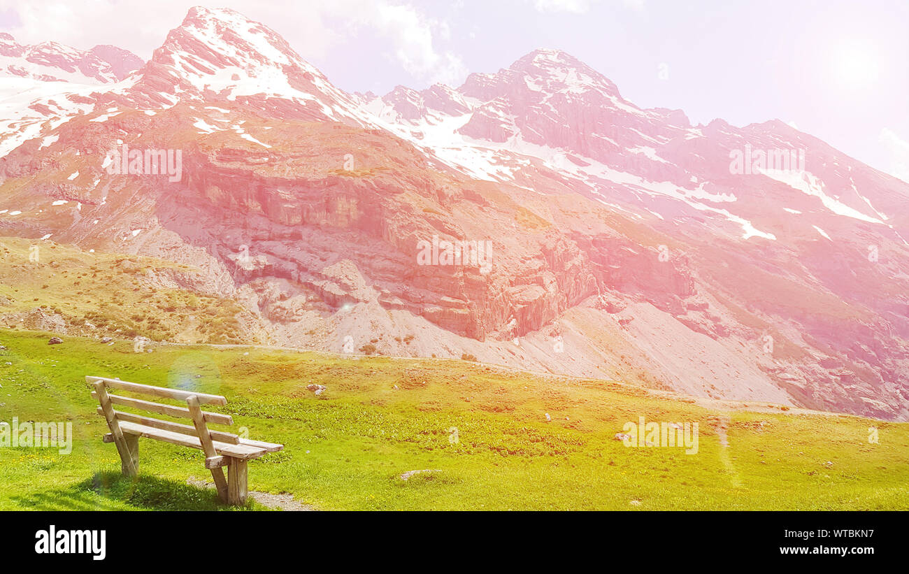 Beautiful natural landscape summer mountain landscape with colorful sunset over snowy mountain range dolomite italy with wooden bench and green meadow Stock Photo