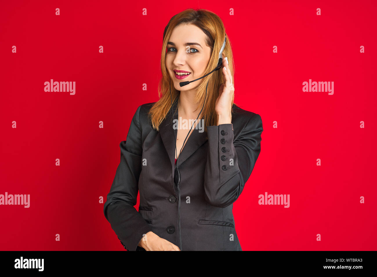 Young beautiful redhead call center agent woman wearing suit using headset Stock Photo