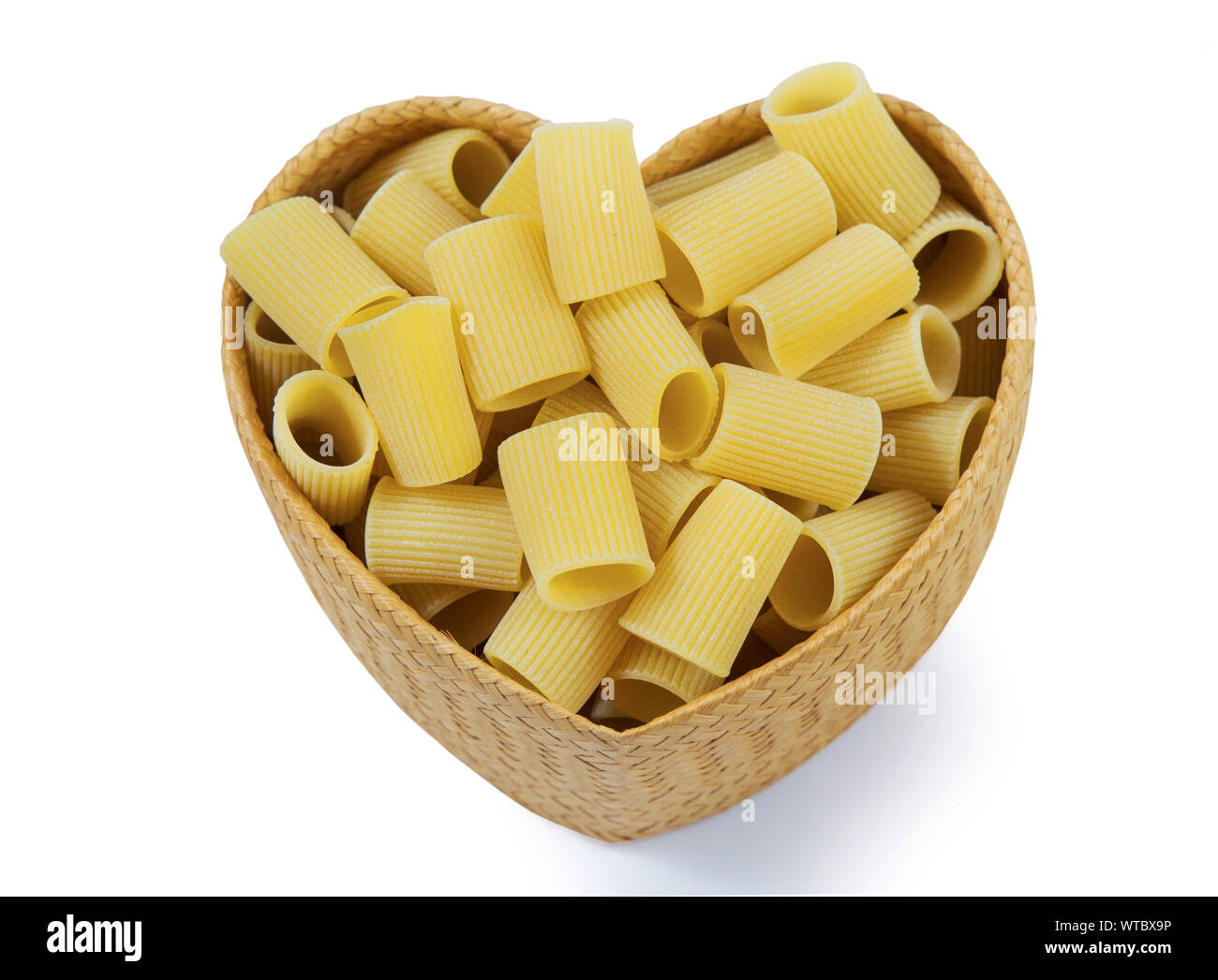 Top view dry pasta penne Italian food in heart shaped bamboo basket isolated white background with clipping path. Stock Photo