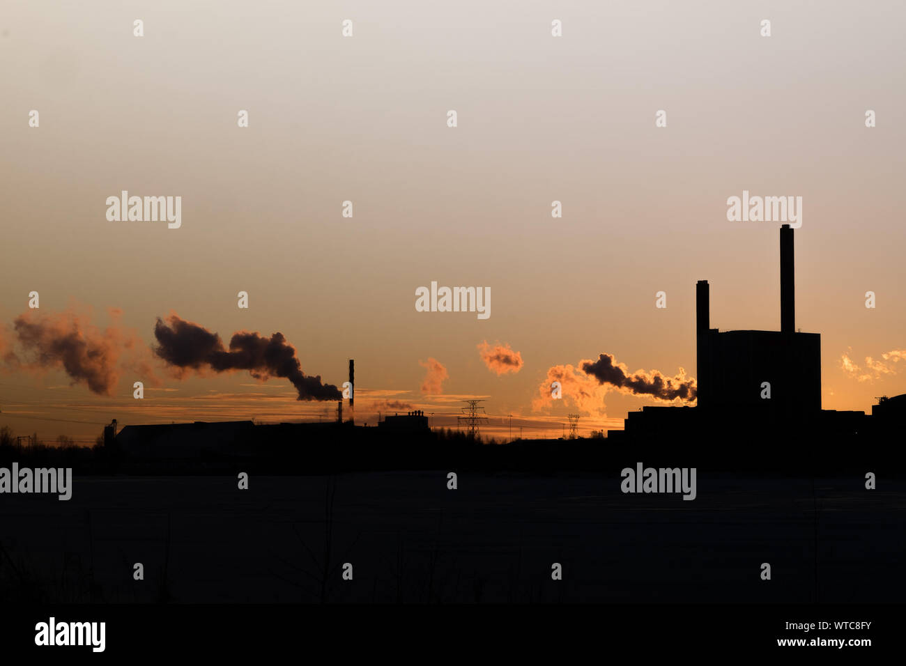 Smoke Emitting From Silhouette Chimneys Against Sky During Sunset Stock Photo