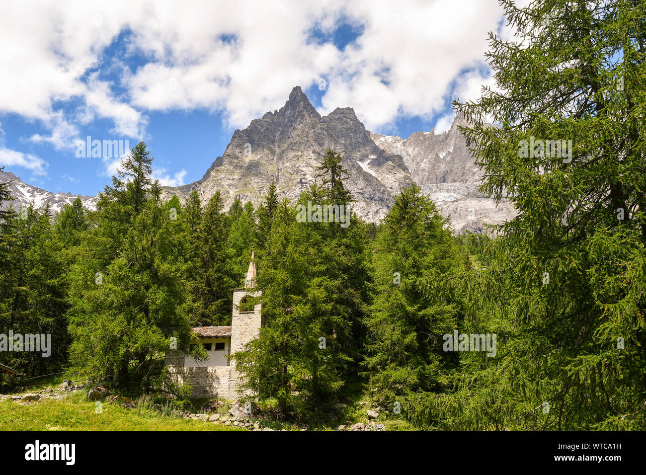Alpine mountain landscape with a stone church in a pine forest at the foot of the Mont Blanc range in summer, Val Ferret, Courmayeur, Aosta, Italy Stock Photo