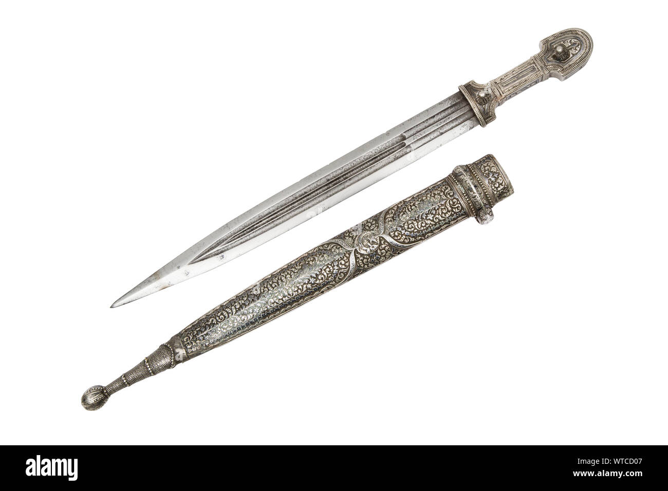 Dagestan dagger (kama) with solid heavy silver mounts decorated with deep floral motif engraving and niello. The blade is decorated with silver inlay Stock Photo