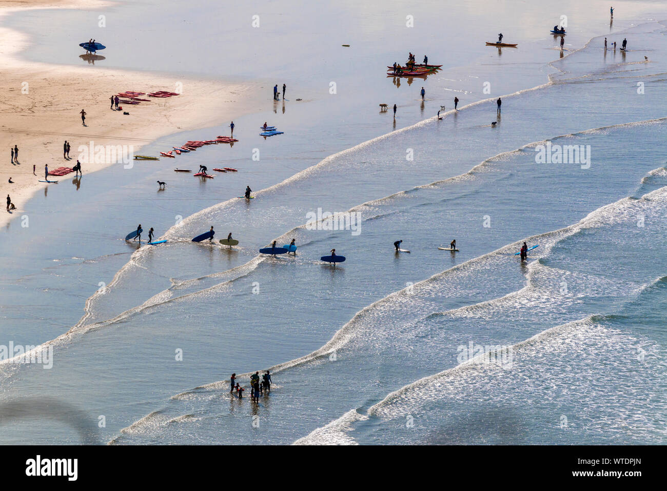 Surfers take to the surf at Saunton Sands, near Croyde, North Devon, England UK Stock Photo