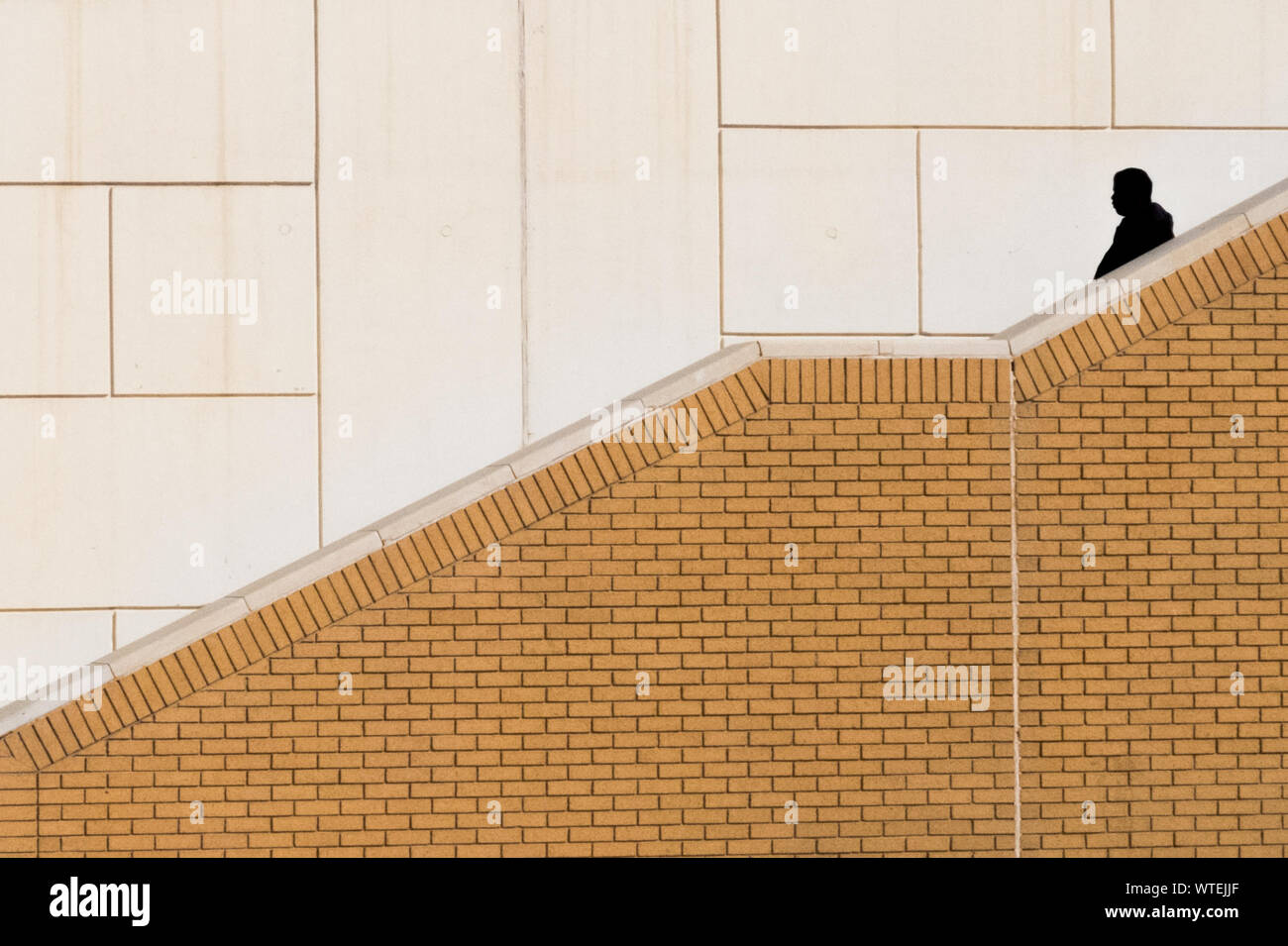 Silhouette Man Walking On Steps Against Wall Stock Photo
