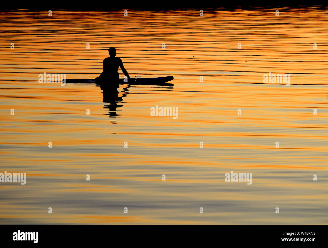 BAGENKOP, DENMARK, 17 JULY 2019: Silhouetted paddle boarder at peace, watching the colorful setting sun from his board on the sea. Relaxation, serene. Stock Photo