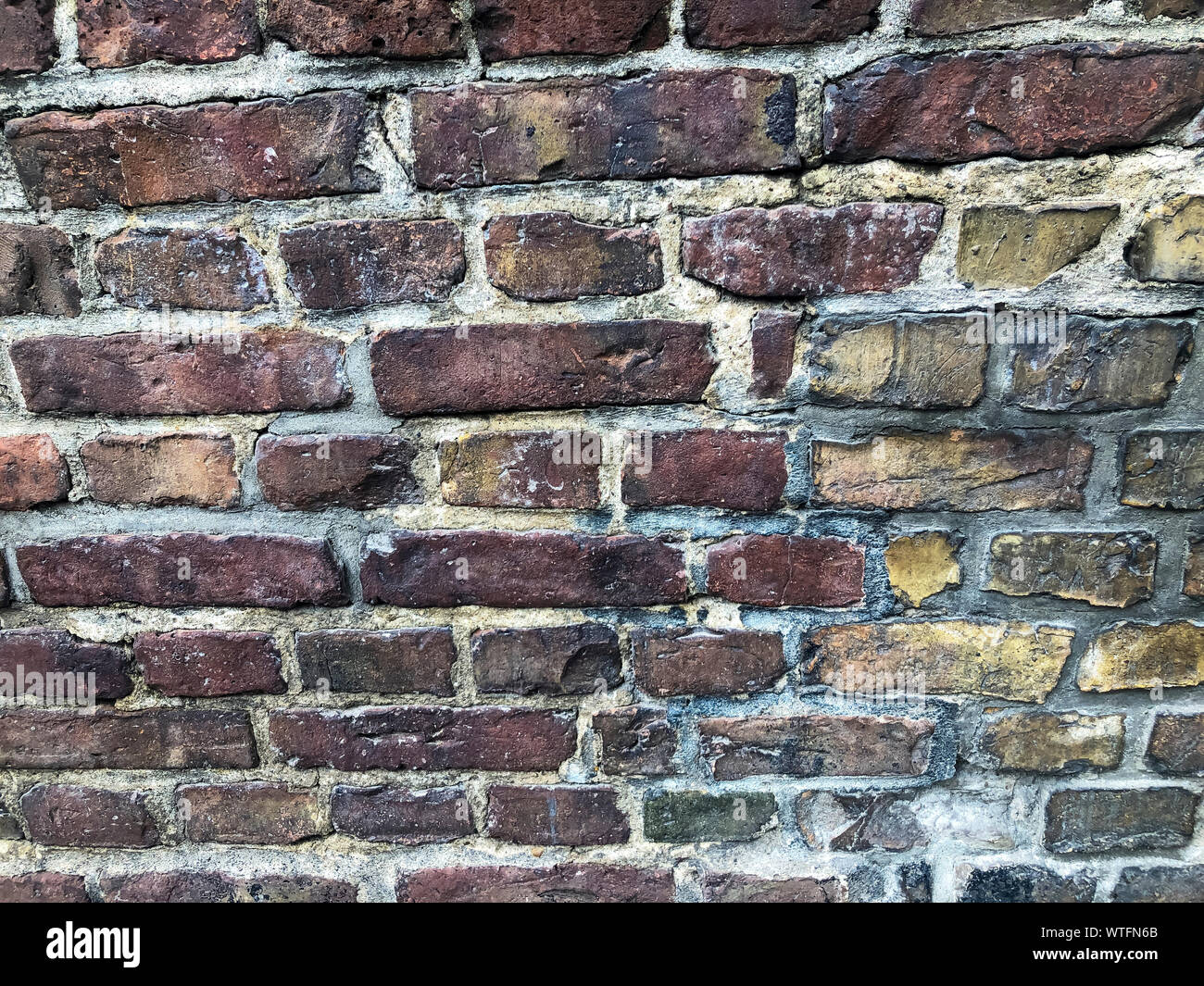 Antique red tempered brick wall. Part of the wall of an ancient building. Stock Photo