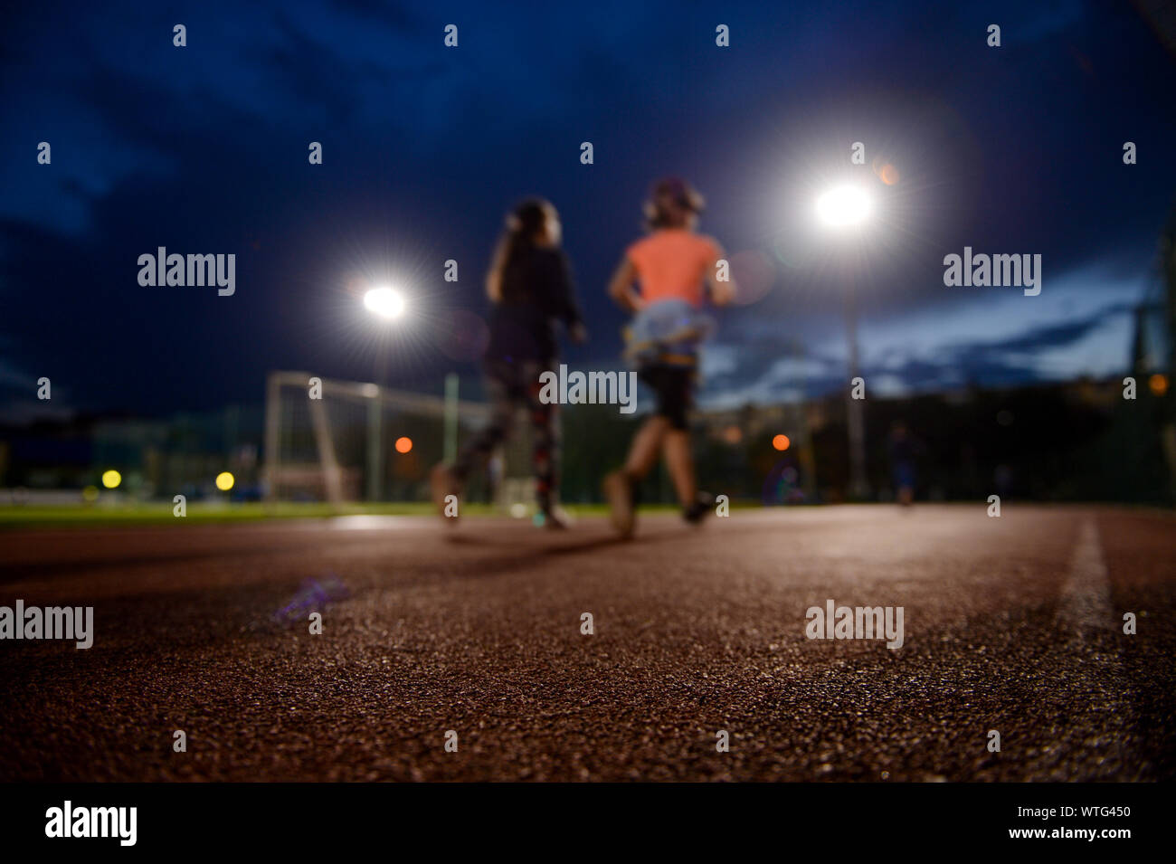 two young females running on outdoor stadium track at twilight Stock Photo