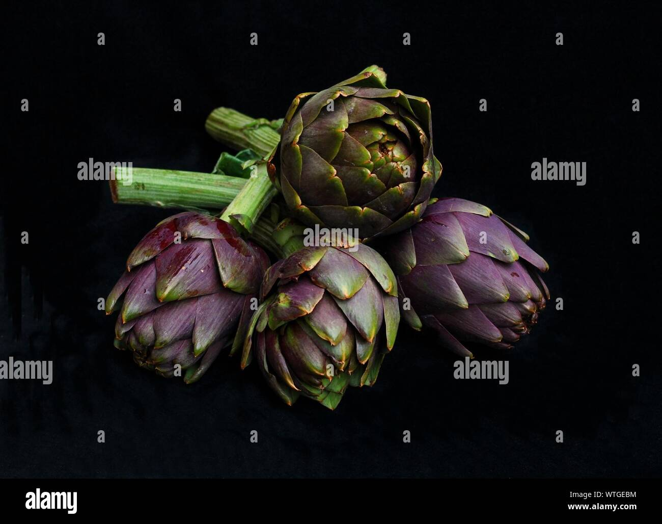 Close-up Of Artichokes Against Black Background Stock Photo