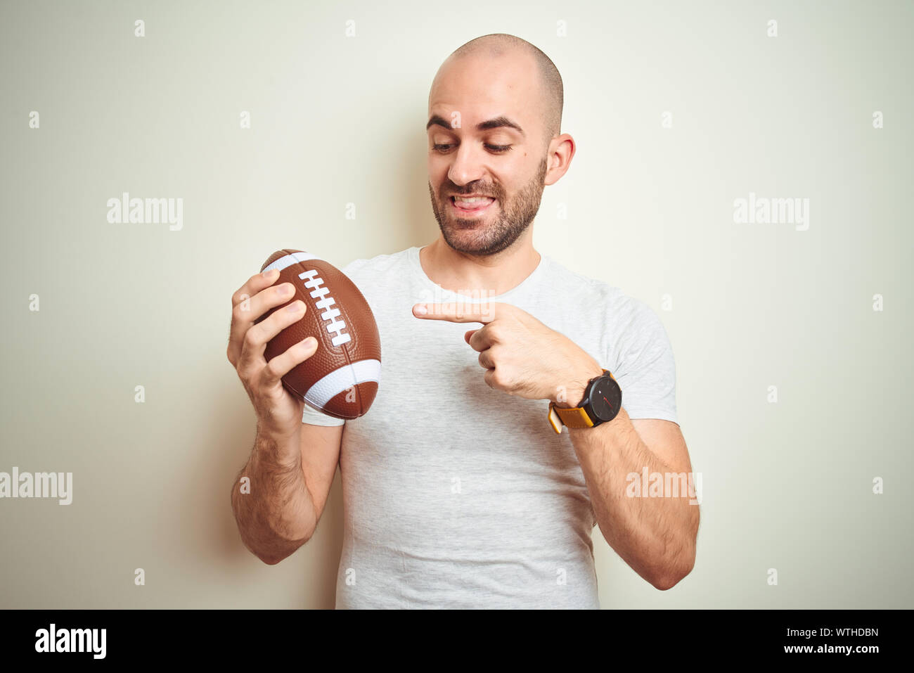 Young man holding rugby american football ball over isolated background very happy pointing with hand and finger Stock Photo