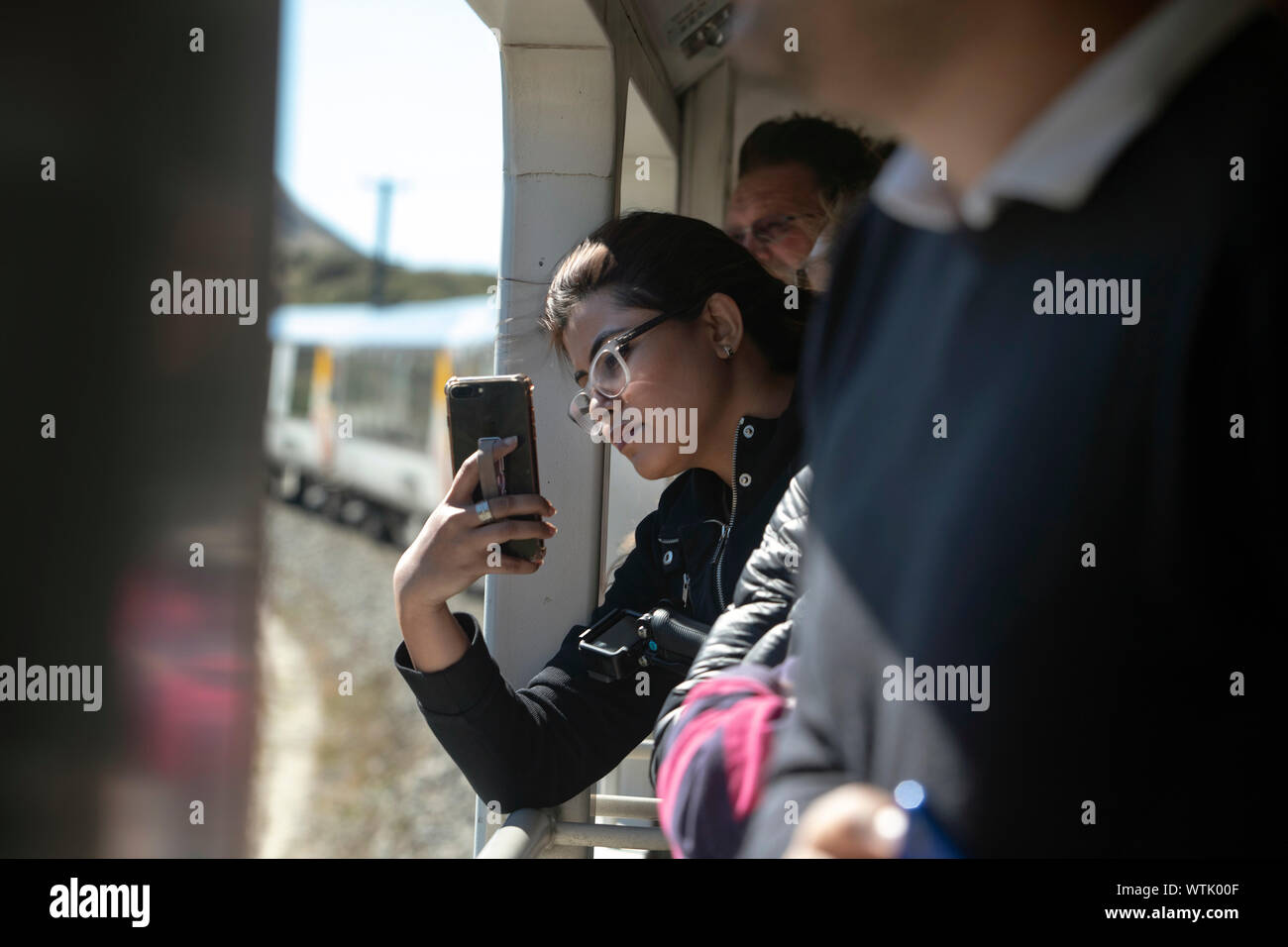 Picture by Tim Cuff - 5 January 2019 - Tranz Alpine train journey from Greymouth to Christchurch, New Zealand: a passenger snaps a selfie-with-train Stock Photo