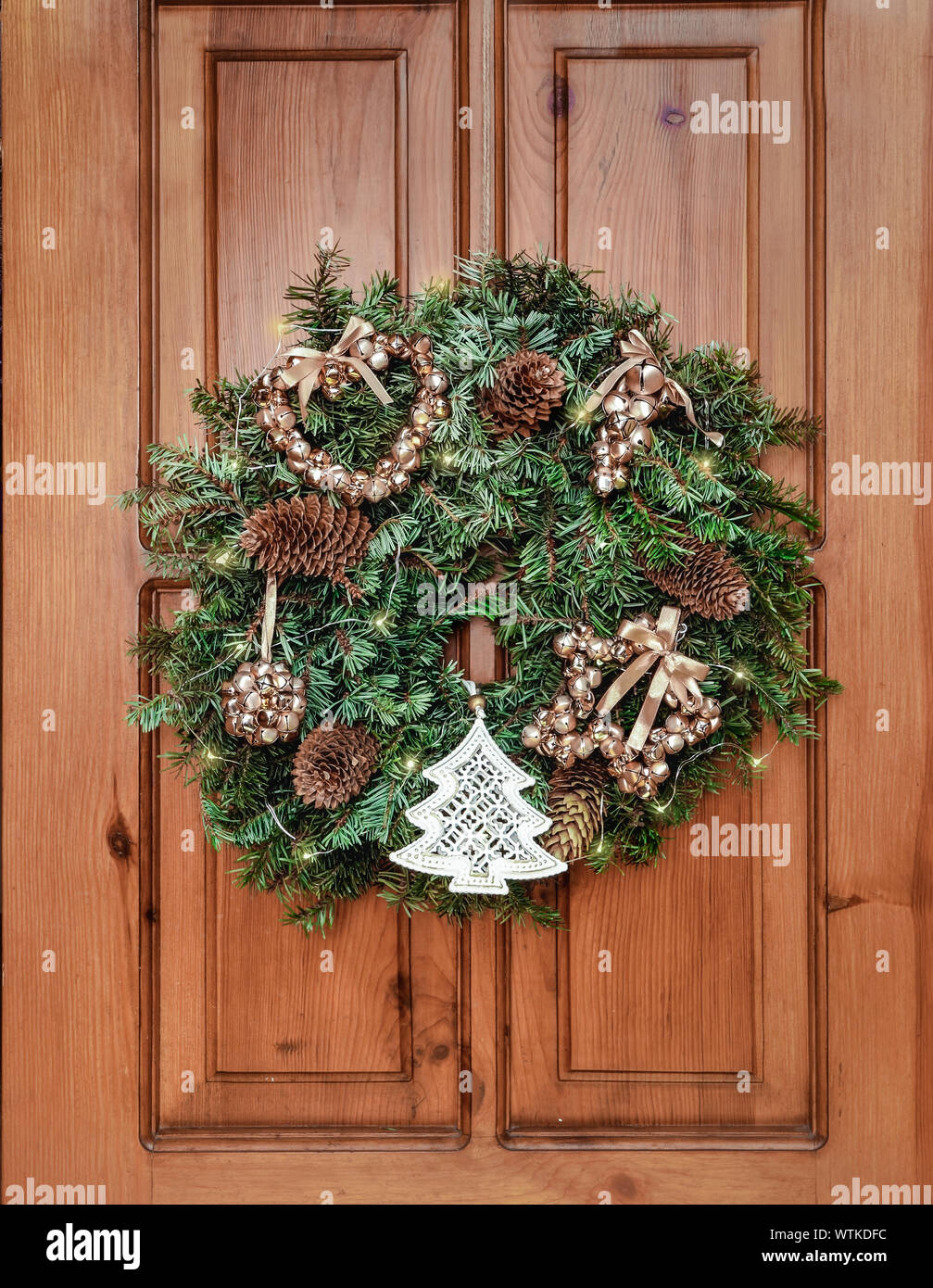 New Year and Christmas decor. Ornament a wreath from branches ate with cones, lights of a garland and gold spheres. Traditional Christmas decoration f Stock Photo