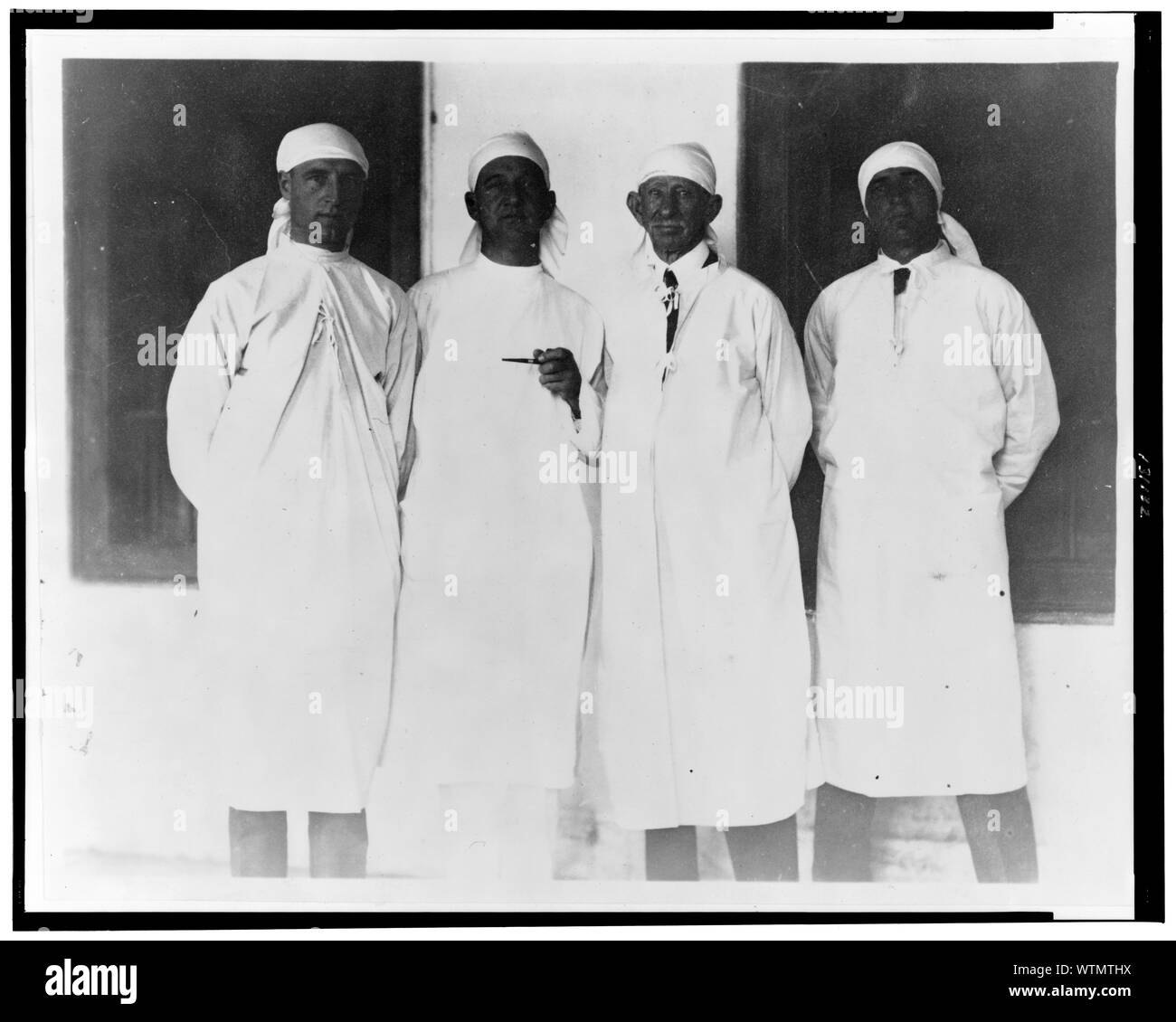 Mr Carpenter Dons A Typhus Uniform And Goes Through A Near East Relief Camp For Greek Refugees From Asia Minor Frank Carpenter Standing With Three Other Men All Wearing White Robes And