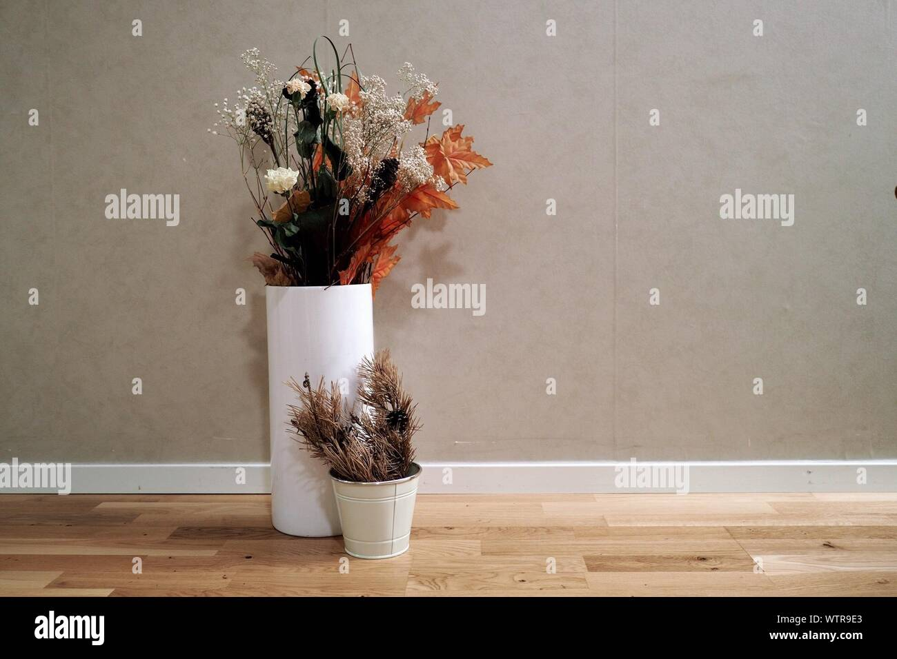 Artificial Flowers In Vase On Floor Against Wall Stock Photo Alamy