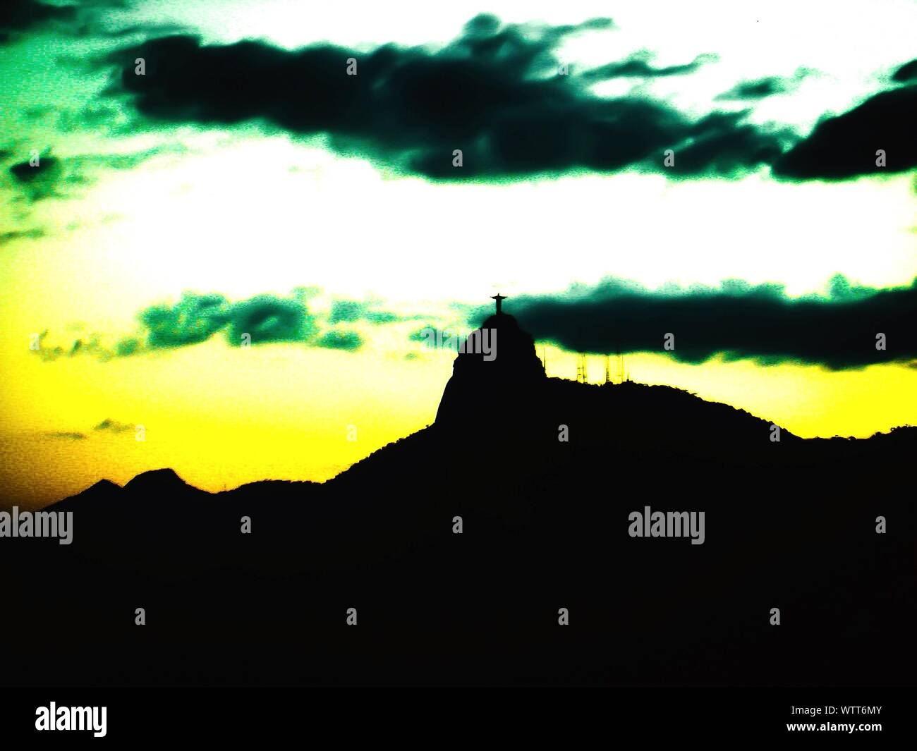 Low Angle View Of Silhouette Christ The Redeemer Statue On Top Of Mountain Against Cloudy Sky Stock Photo