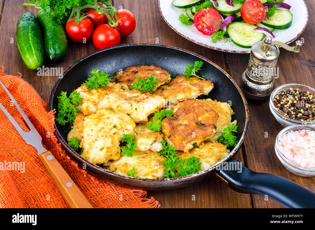 Fried meat pancakes in pan, vegetables, wooden background Stock Photo