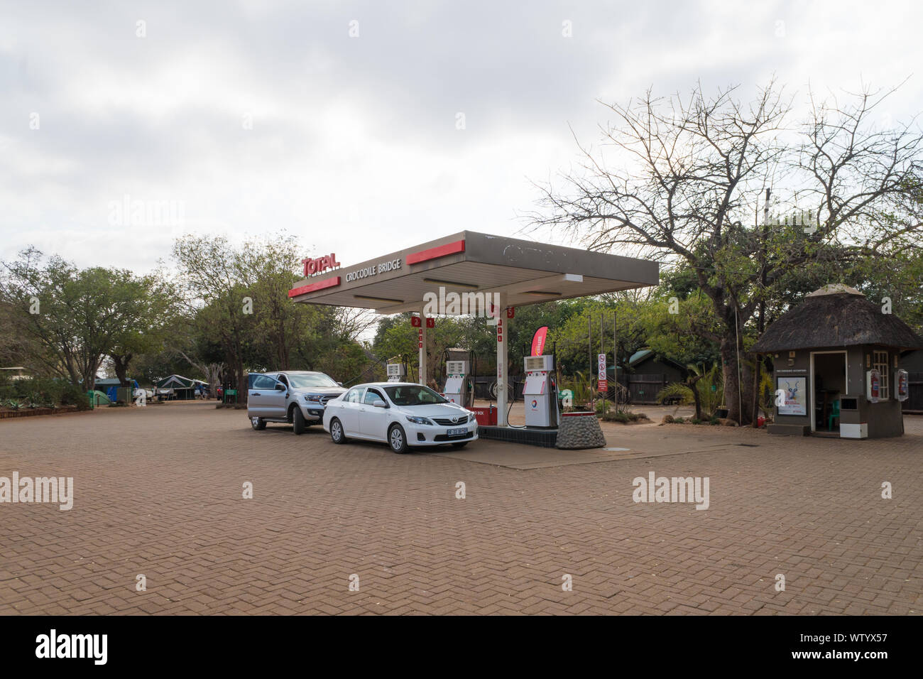 cars or vehicles at a Total petrol or gas station filling up at the petrol pumps at Crocodile Bridge, Kruger National Park, South Africa Stock Photo