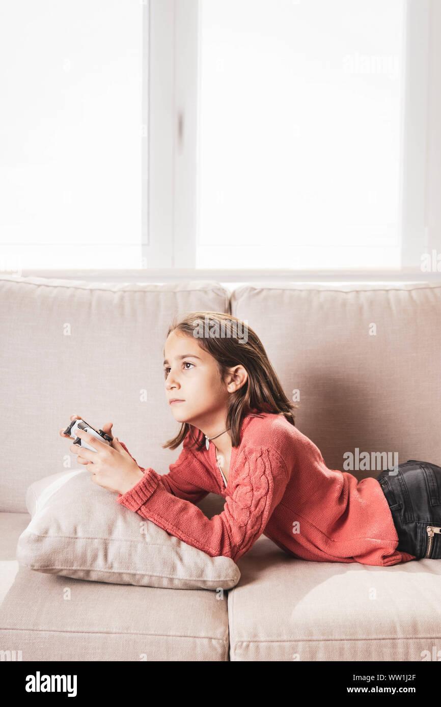 Niña jugando en casa con la videoconsola tumbada en el sofá Stock Photo