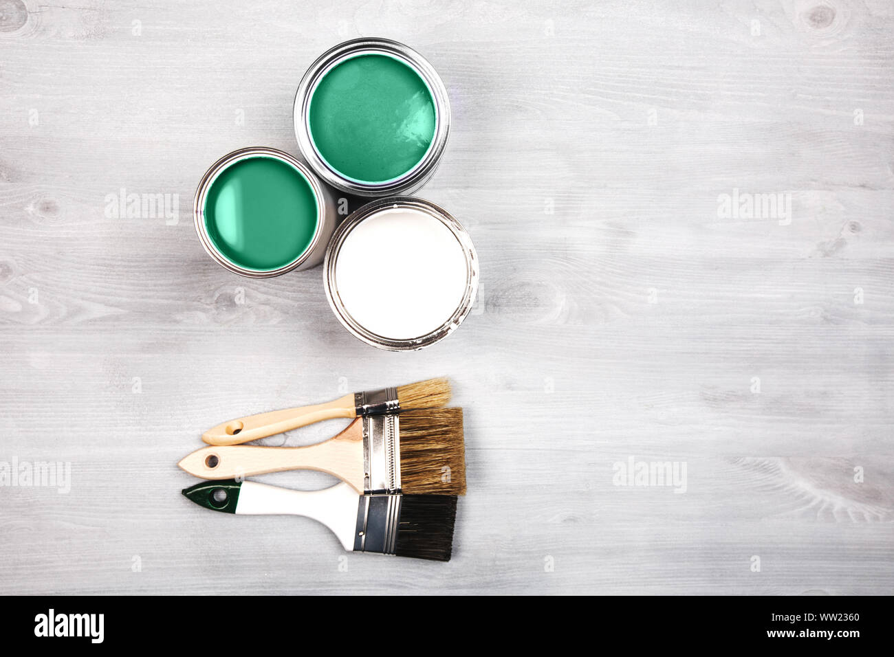 Green paint cans and colored brushes on white wooden background Stock Photo