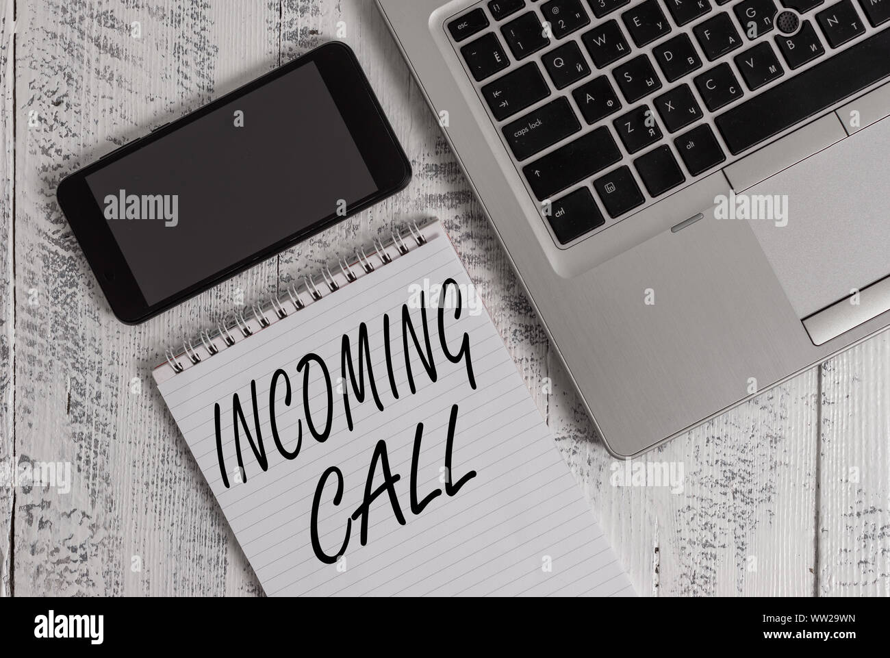 Handwriting text Incoming Call. Conceptual photo Inbound Received Caller ID Telephone Voicemail Vidcall Metallic laptop blank ruled notepad smartphone Stock Photo