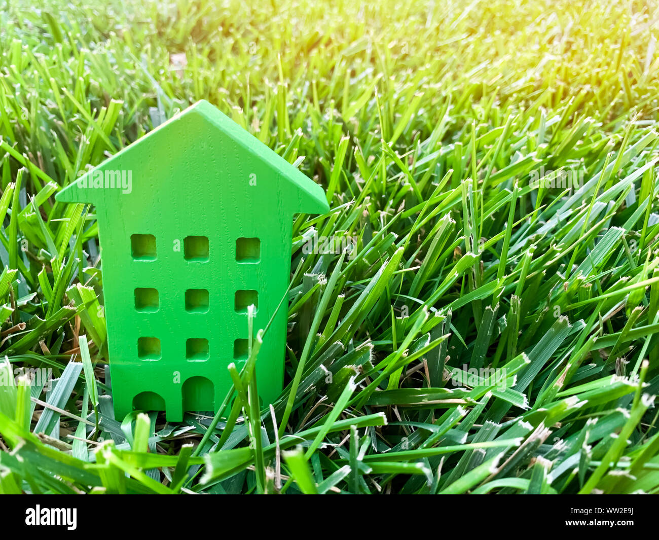 Miniature wooden house on grass  Real estate concept  Eco