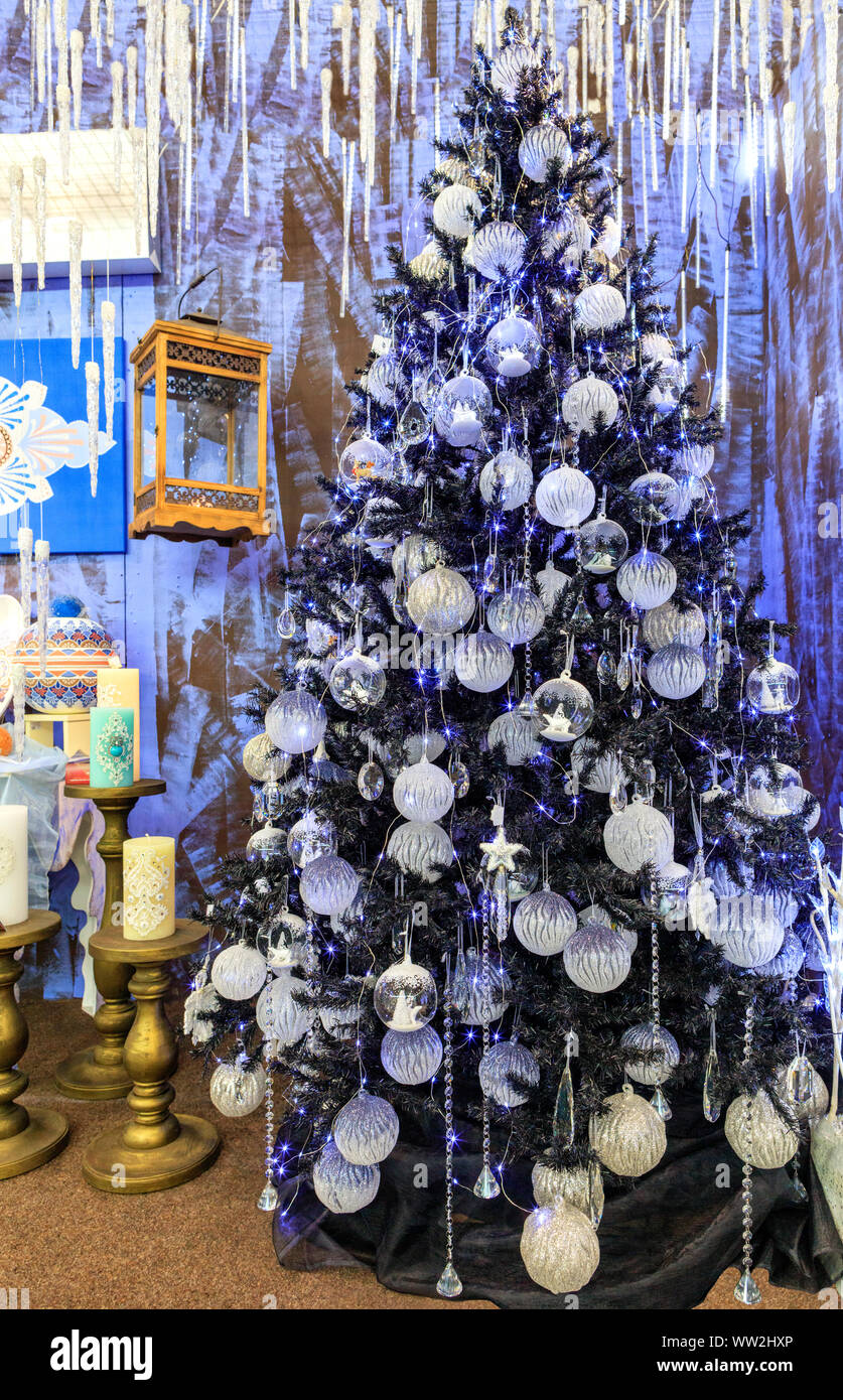 A Collection Of Silver Stars Christmas Balls Christmas Baubles Decorative Icicles Is Illuminated By Blue Lights On A Slender Christmas Tree Stock Photo Alamy