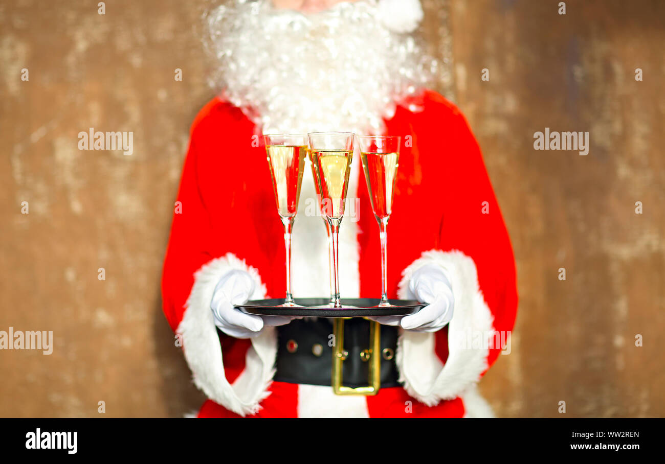 Santa Claus holding champagne glasses on the tray. Closeup Stock Photo