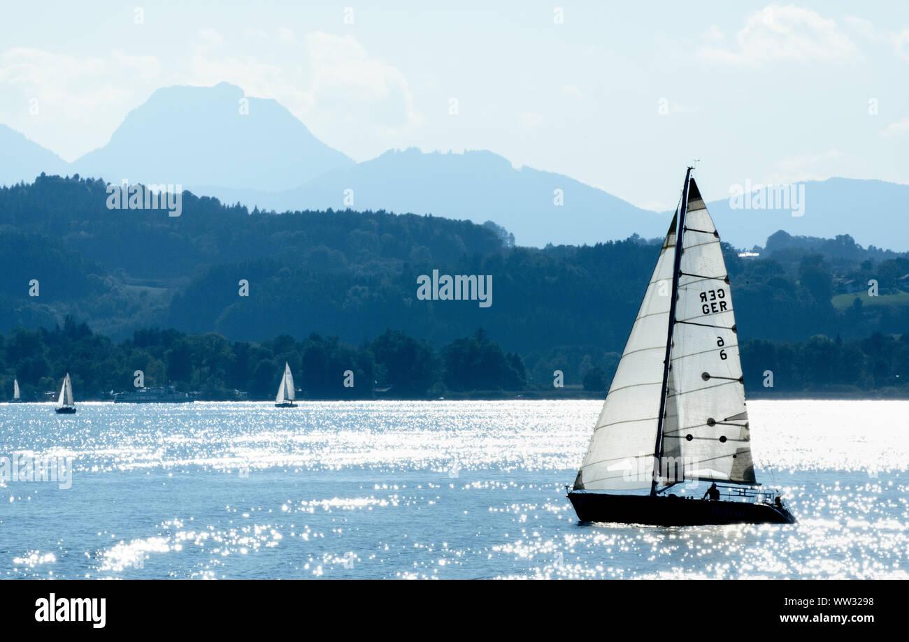 12 September 2019, Bavaria, Prien: The water on Lake Chiemsee glitters around a sailing boat. Photo: Matthias Balk/dpa Stock Photo