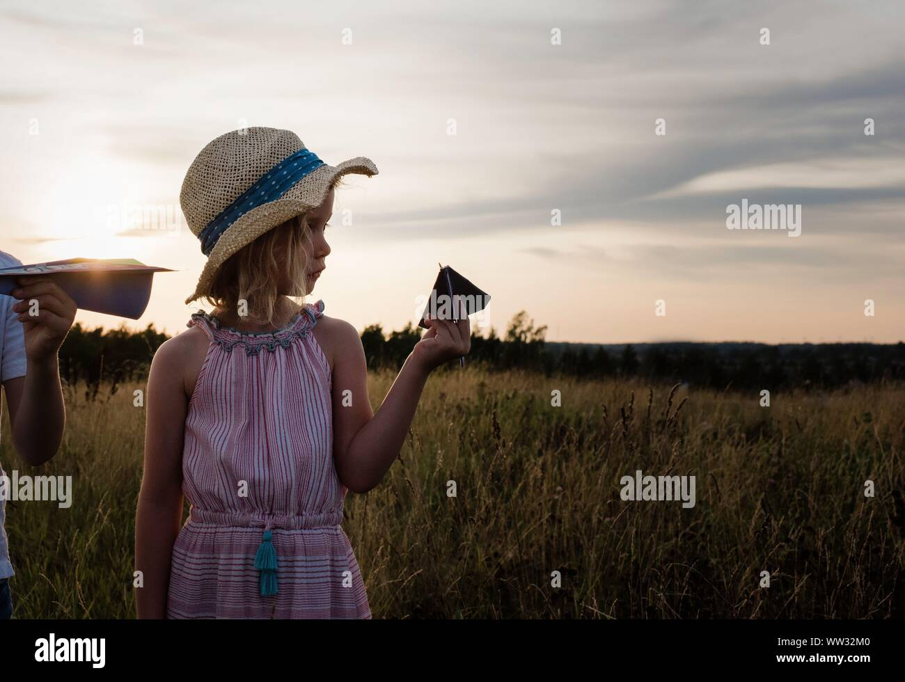 profile of a young girl holding a paper plane in a meadow at sunset Stock Photo