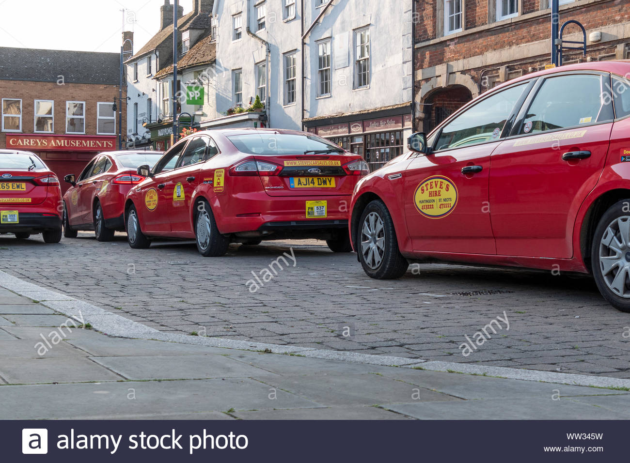Steve's Mini Cab / taxi hire vehicles in a row at St Neots in Cambridgeshire, England, UK Stock Photo