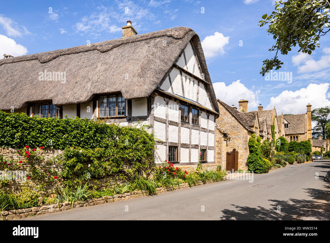 Old half timbered buildings and stone houses beside the lane in the Cotswold village of Stanton, Gloucestershire UK Stock Photo