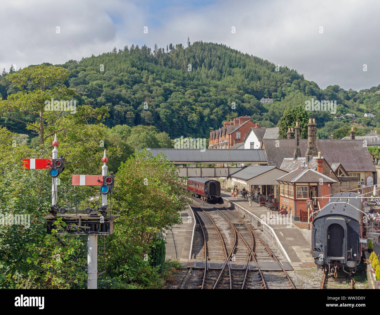 Llangollen railway station underneath a tree covered hill.  Railway carriages are in a siding and there is a signal in the foreground. Stock Photo