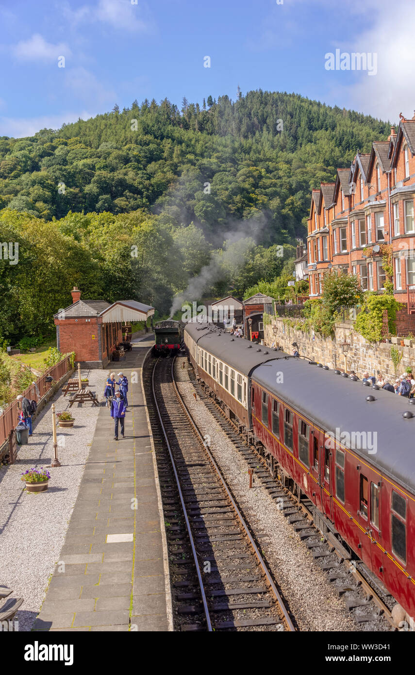 Llangollen railway station underneath a tree covered hill.   Railway carriages are beside a platform with a train engine on an adjacent track. Stock Photo