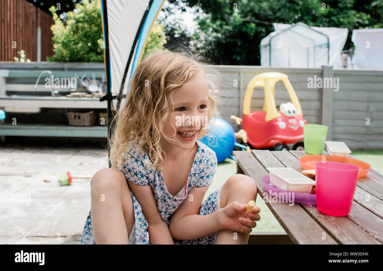 young blonde girl smiling eating lunch at home outside in england Stock Photo