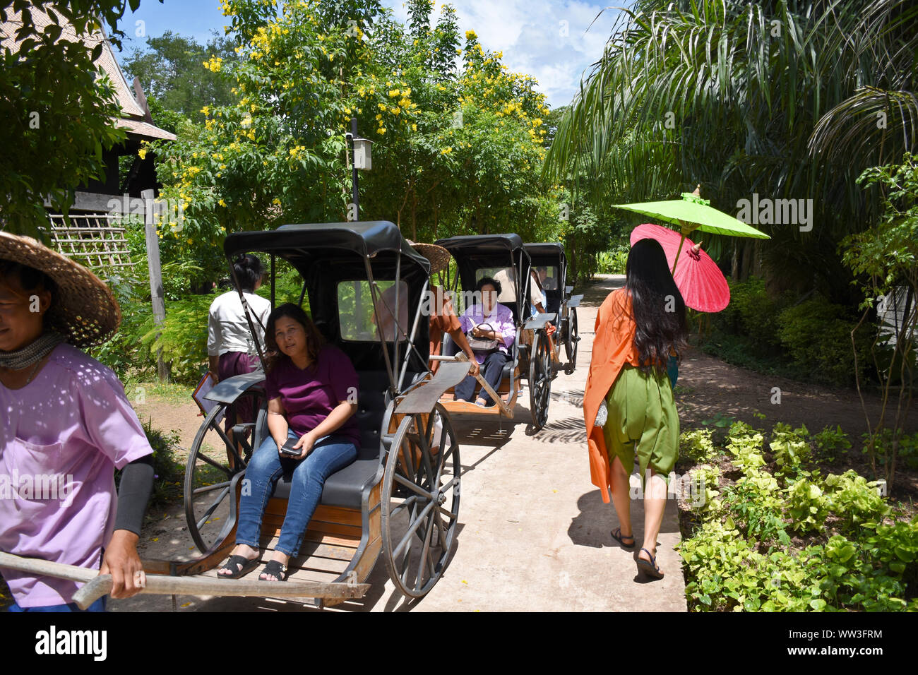 """Kanchanaburi, Thailand, 09.09.2019: Locals are transporting tourists/guest in traditional Rickshaws in """"Mallika City R.E. 124"""", the heritage, retro-ci Stock Photo"""