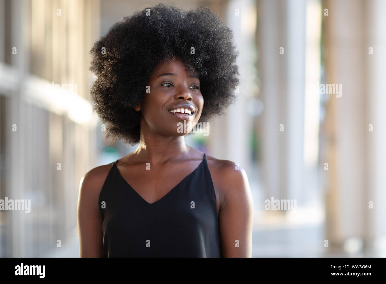 Portrait of smiling young black woman with sunlight flare and copy space Stock Photo