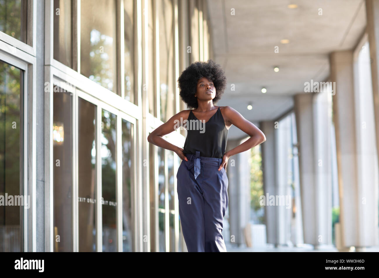 A young fashionable Afro-American woman walking down the street with her hands on her waist Stock Photo