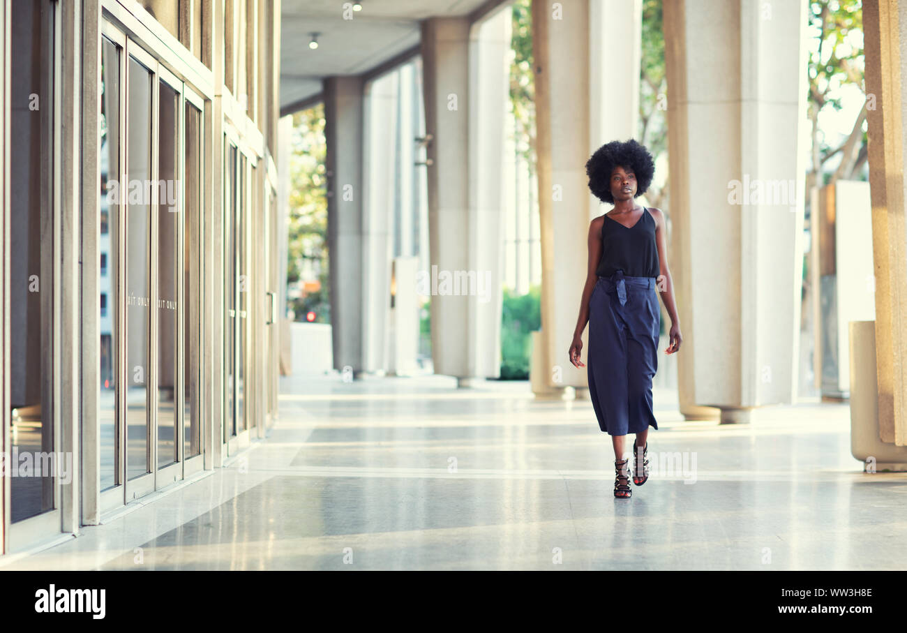 A young fashionable Afro-American woman confidently walking down the hall outside the financial building Stock Photo