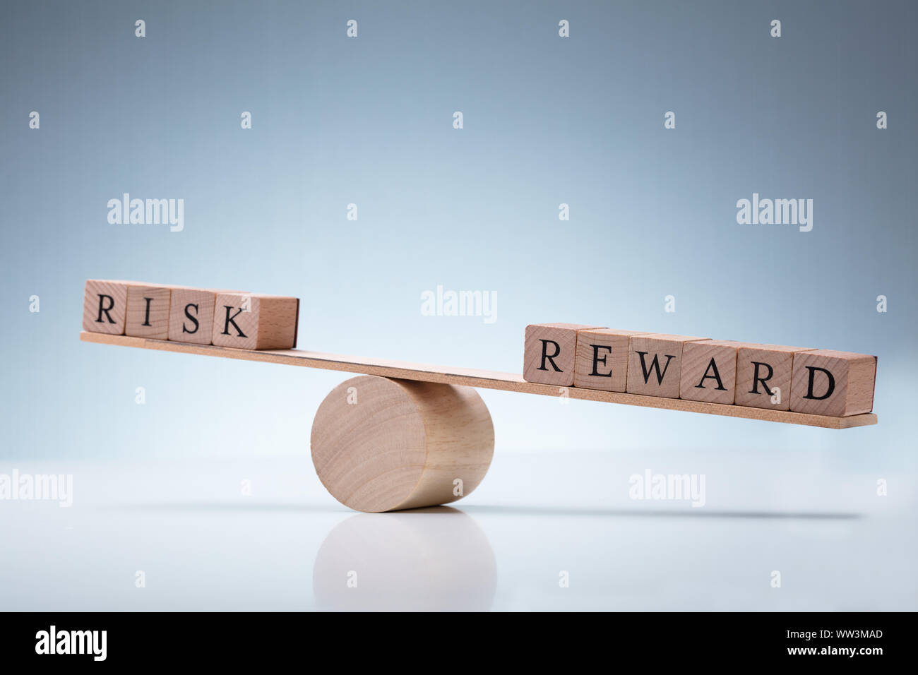 Close-up Of A Wooden Seesaw Showing Imbalance Between Risk And Reward On Reflective Background Stock Photo
