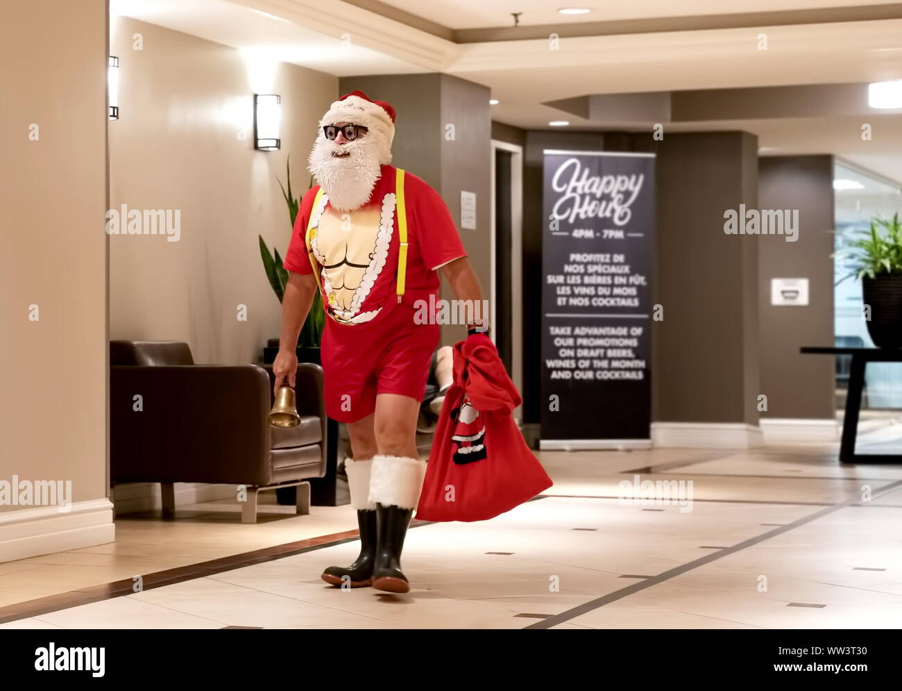 Montreal, Canada. Jul 2019. Man in a Santa costume exposing some hard body workout abs leaving a booze bar after an Happy Hour event. Stock Photo