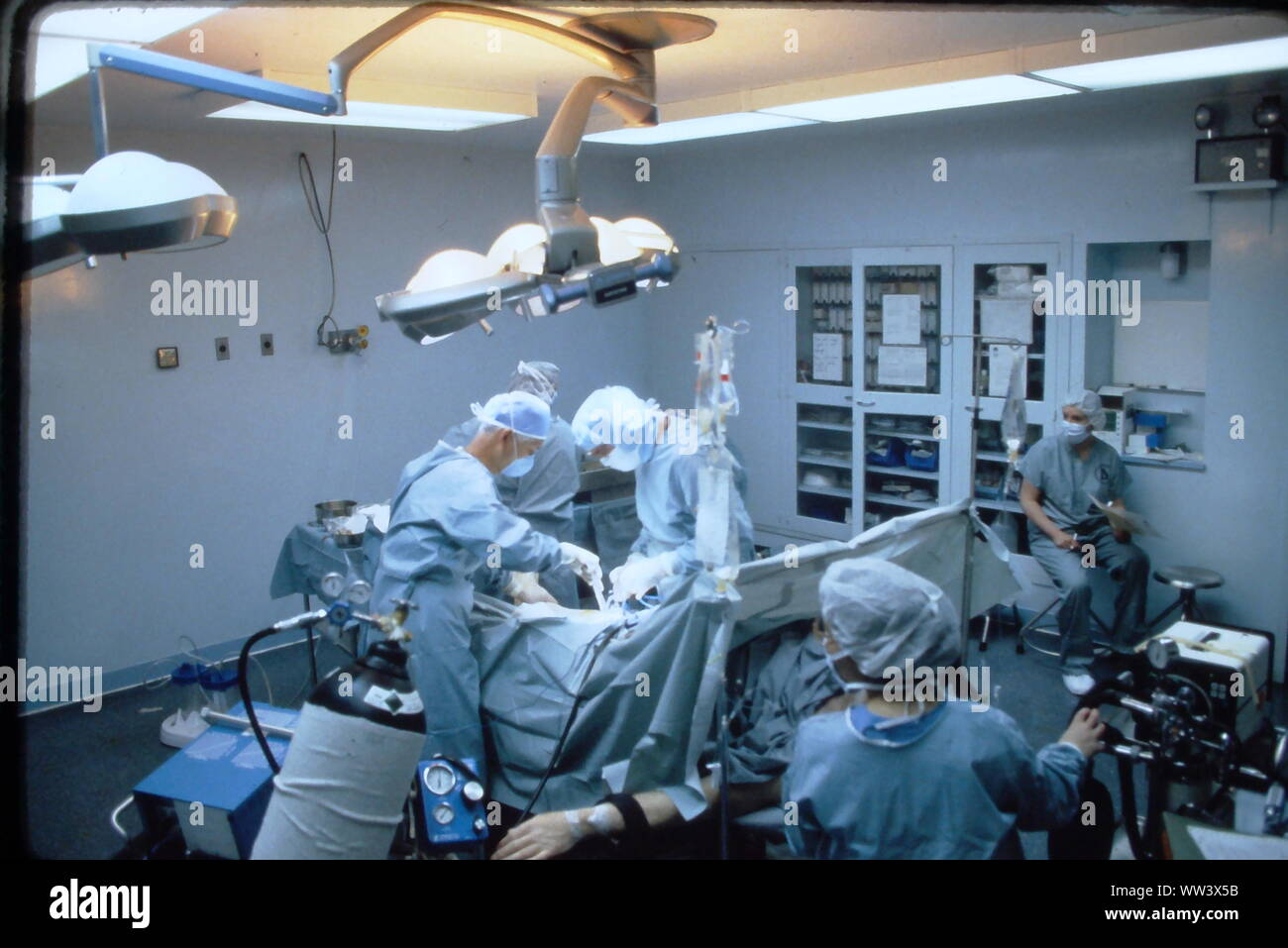 Surgeons performing knee replacement  in sterile surgical scene. Stock Photo