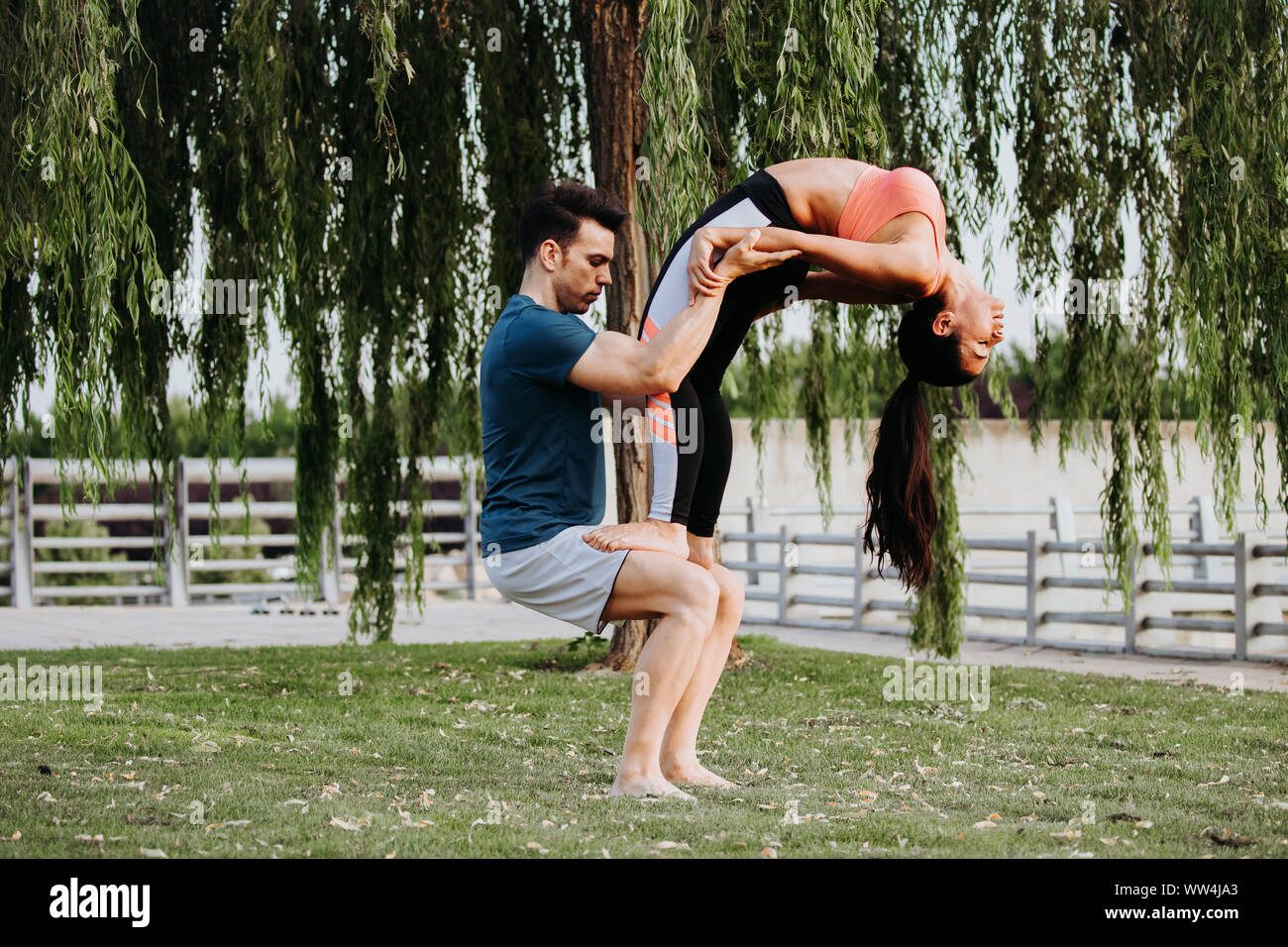 Latin Woman And Caucasian Shadow Do Yoga Exercises In A Park In Madrid Balance And Concentration In Couple Stock Photo Alamy