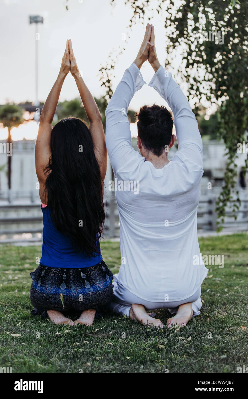 Caucasian man and Latin woman meditate in a park in Madrid. Concentration and relaxation in couple. Stock Photo